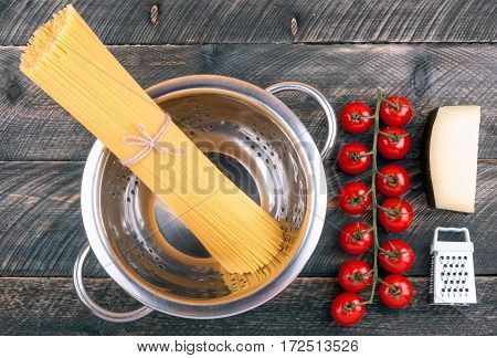 Spaghetti pasta tomatoes cheese colander and grater on old rustic background. Ingredients for cooking pasta. Top view