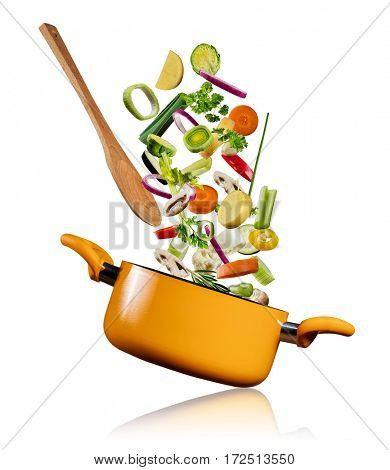 Fresh vegetables flying into a pot with wooden spoon, isolated on white background