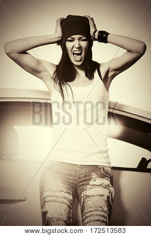 Angry punk woman standing beside her car. Stylish fashion model outdoor