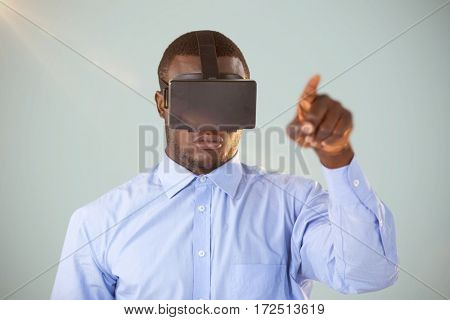 Man standing while wearing virtual reality headset against grey background