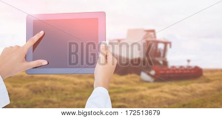Doctor using tablet pc against view of a harvester