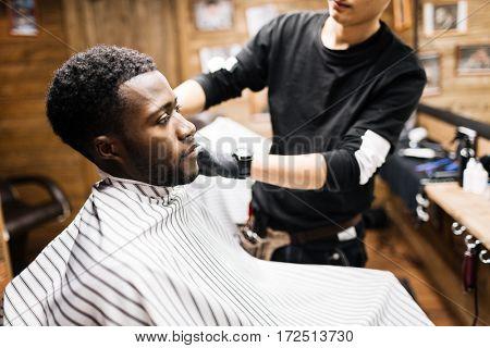 Haidresser preparing young man for haircut