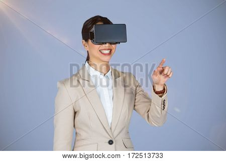 Smiling businesswoman pointing while wearing virtual video glasses against grey background