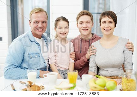 Affectionate family sitting by kitchen table