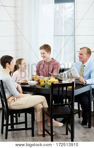 Family talking by kitchen table after meals