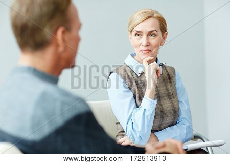 Confident psychologist listening to her patient