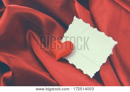Red heart and blank white post cards, lying on silk