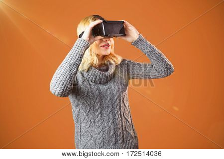 Woman with blond hair using virtual reality headset against orange background