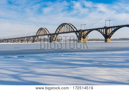 Winter landscape with Merefo-Hersonsky bridge over frozen Dnepr river on the same city Ukraine