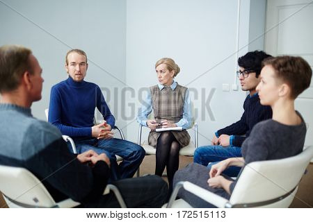 Young man explaining details of his situation to group of people