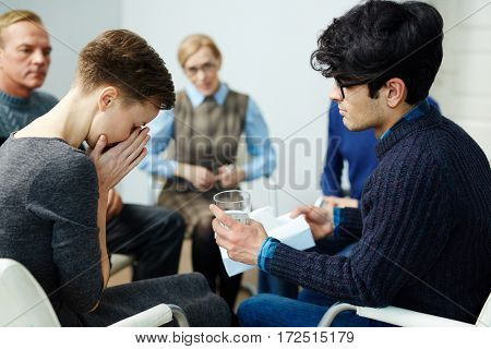 Young man giving glass of water to groupmate during psychological session
