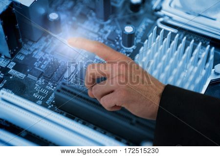 Businessman hand gesturing against micro parts of mother board
