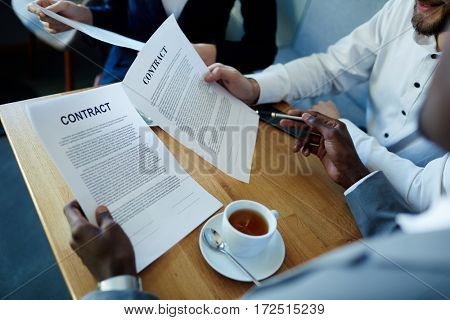 Partners reading business contracts before signing