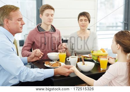 Family of four giving thanks to Lord by dinner table