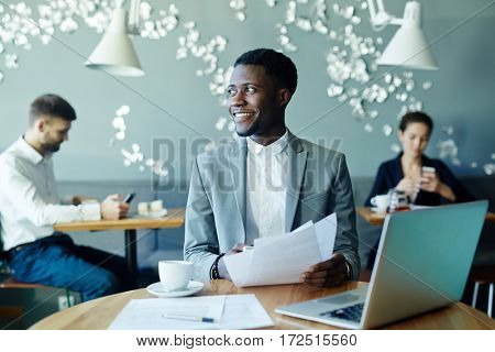 Confident leader with papers having break in cafe