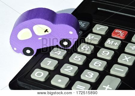 Car and calculator over white background . The concept of changes in car prices in the market
