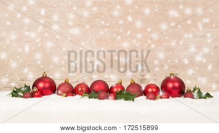 Row of red christmas balls decoration in the snow on a wooden background while snow is falling