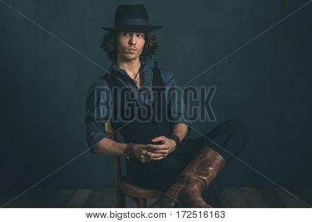 Artistic Alternative Vintage Man Wearing Black Hat. Sitting On Wooden Chair In Studio.