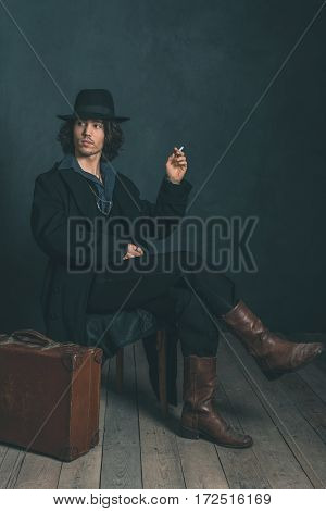 Artistic Alternative Vintage Man Wearing Black Hat And Coat. Smoking Cigarette. Sitting On Wooden Ch