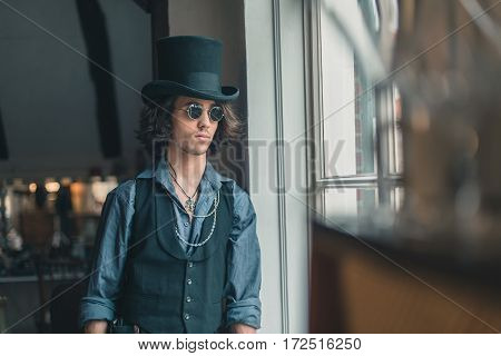 Artistic Alternative Vintage Man With Sunglasses And Hat Looking Out Window.