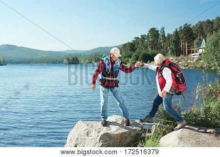 Senior man helping his wife while hiking