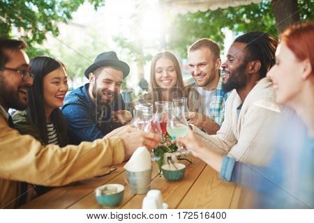 Group of friendly hipsters with drinks enjoying time in cafe