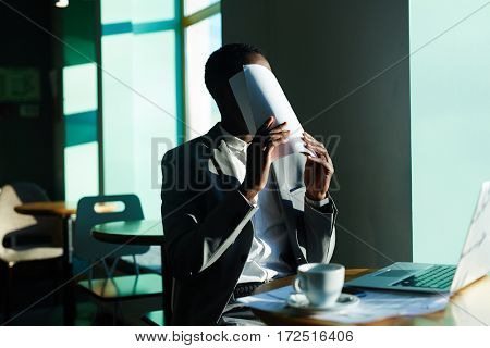 Businessman covering his face by papers