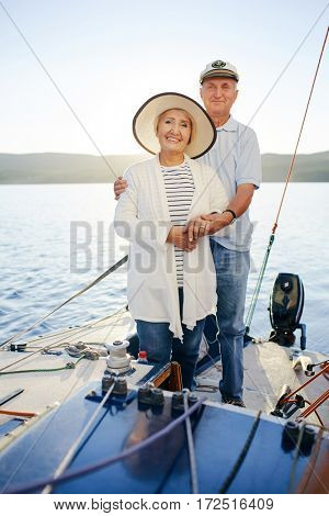 Aged couple sailing on yacht during voyage