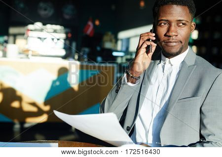 Busy broker with document speaking on smartphone