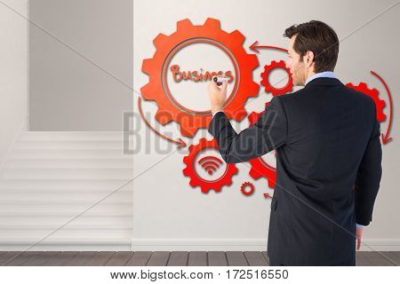 Businessman standing back to camera writing with marker against empty room