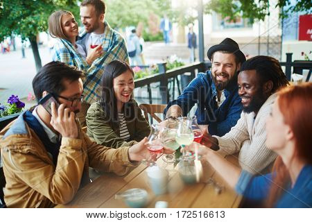 Youthful friends toasting with drinks during hangout