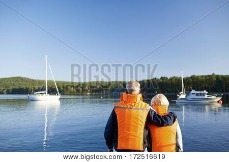 Affectionate seniors in protective vests looking at yacht in the lake