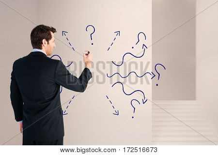 Businessman standing back to camera writing with marker against staircase amdist wall