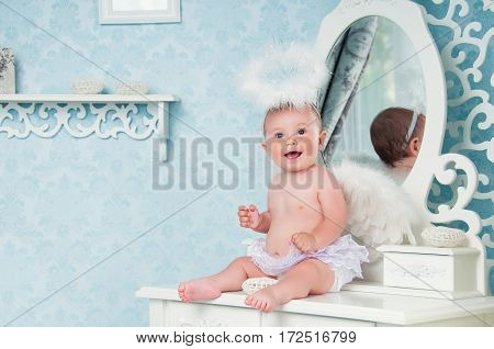 Little angel smiling and sitting on the dressing table.