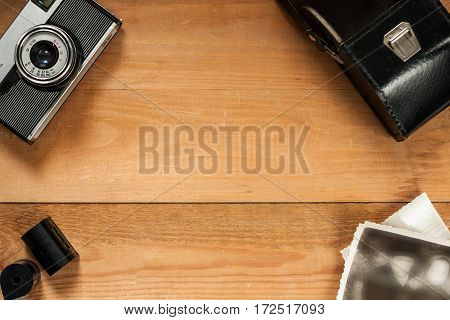 Vintage Old Retro Camera Black Leather Bag Fhotos And Film On Wooden Brown Board Top View And Copyspace.