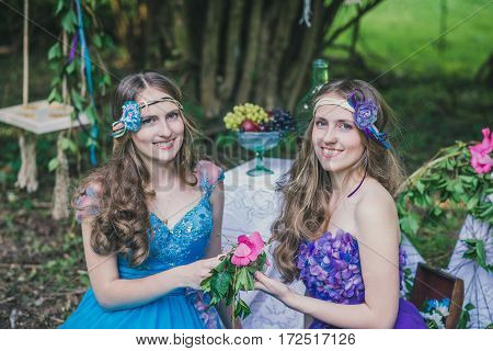 two adult sisters are twins with flowers in the summer garden