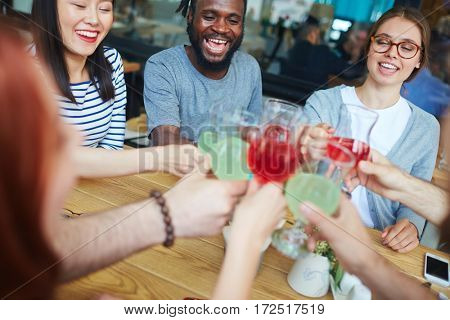 Multi-ethnic group of young buddies cheering up with drinks