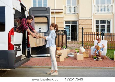 Portrait of young woman helping her husband load cardboard boxes into moving van while their daughter waiting with other belongings in front of house