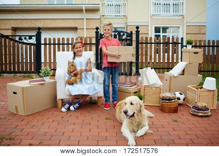 Portrait of neat happy children, boy and girl and their pet golden retriever outside, in front of their new house, ready to move in