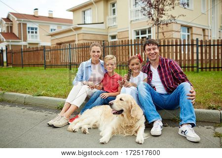 Portrait of happy family with two children, boy and girl, and their golden retriever dog sitting outside on green grass lawn in front of their new big house