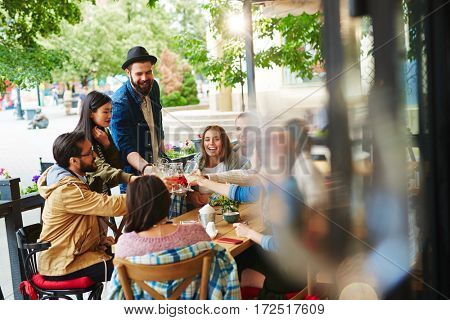 Group of young friends cheering up with drinks