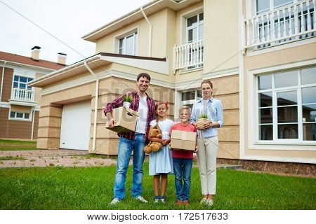 Portrait of successful family with two children standing together holding cardboard boxes on green grass lawn in front of their new house, smiling brightly looking at camera, ready to move in