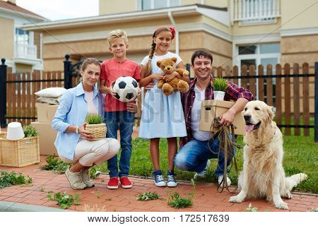 Portrait of happy family of four and their golden retriever dog standing outside holding cardboard boxes and personal belongings in front of their new house, smiling brightly, ready to move in