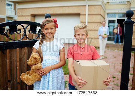Portrait of neat happy children, boy and girl, standing holding cardboard box and toys in driveway of their new house, smiling brightly and looking at camera, ready to move house