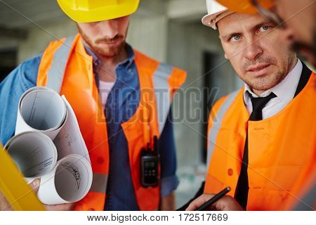Portrait of foreman inspector talking to two workmen wearing protective vests and hard hats, discussing construction progress on site
