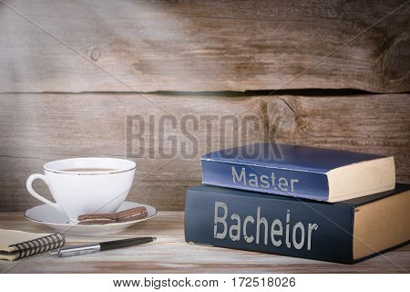Bachelor and Master. Stack of books on wooden desk.