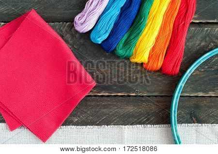 Accessories for embroidery. Canvas hoop for embroidery and thread floss on a wooden background