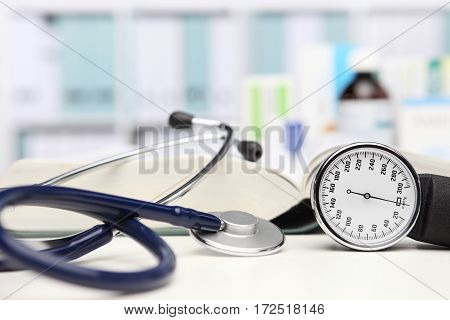 doctor desk with medical equipment stethoscope and clinic tonometer blood pressure measurement drugs in background