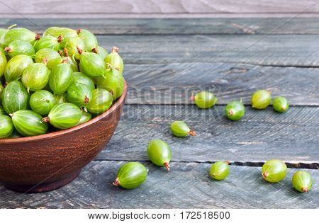 Fresh green gooseberries in a ceramic bowl. Gooseberry close up. Rustic style