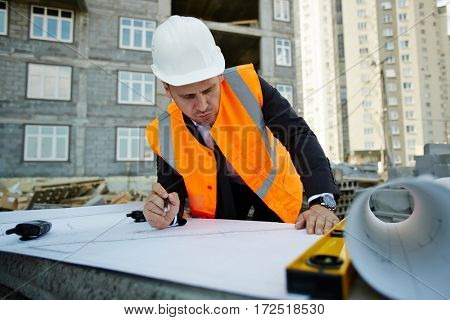 Portrait of construction foreman wearing vest over formal suit busy correcting blueprints and making measurements leaning over papers at development site